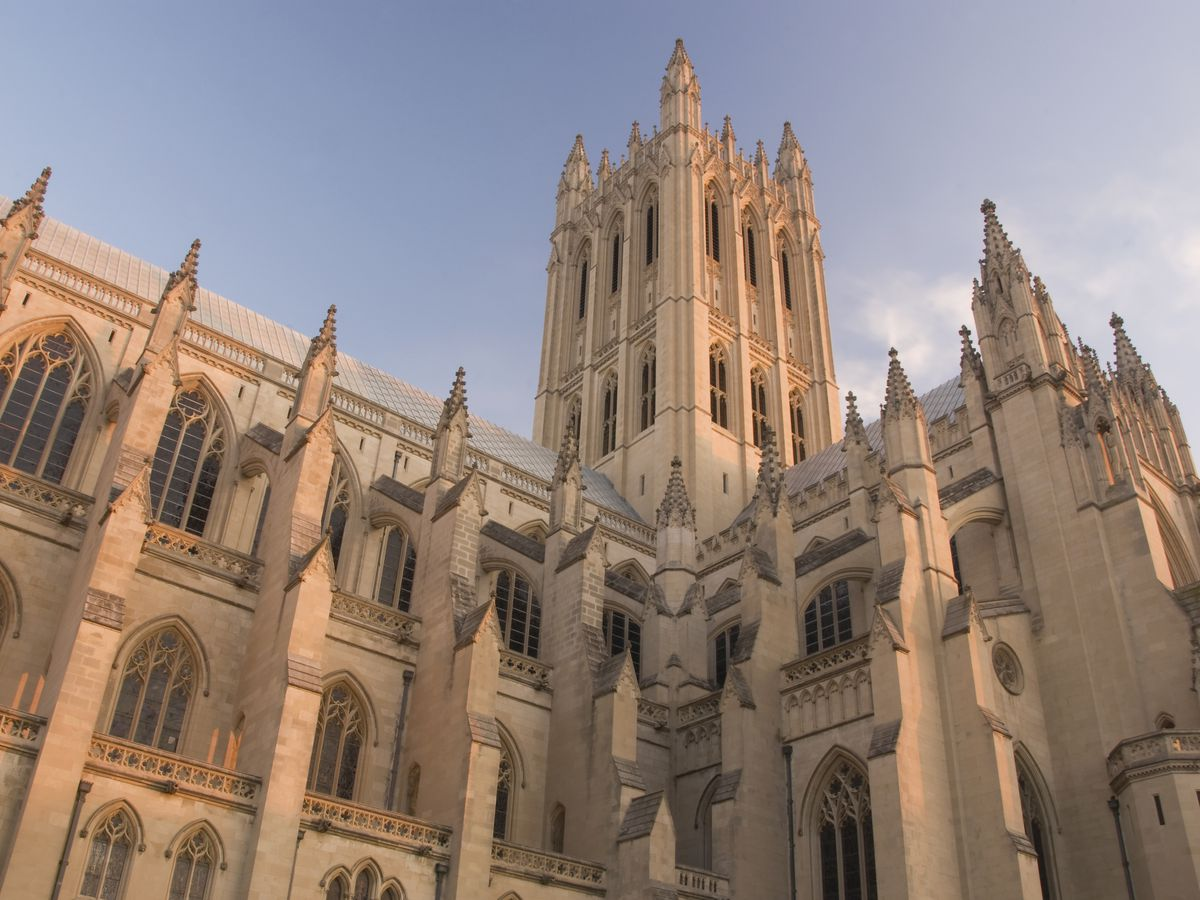 The facade of a neo-Gothic cathedral shown at sunrise. It has intricate spires and windows.