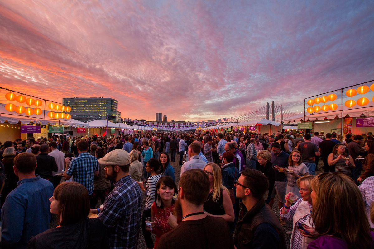 A massive crowd  of festival-goers stand in Feast's Night Market, with lines of paper lanterns above a line of stalls. Sunset falls over the Tilikum Bridge in the background