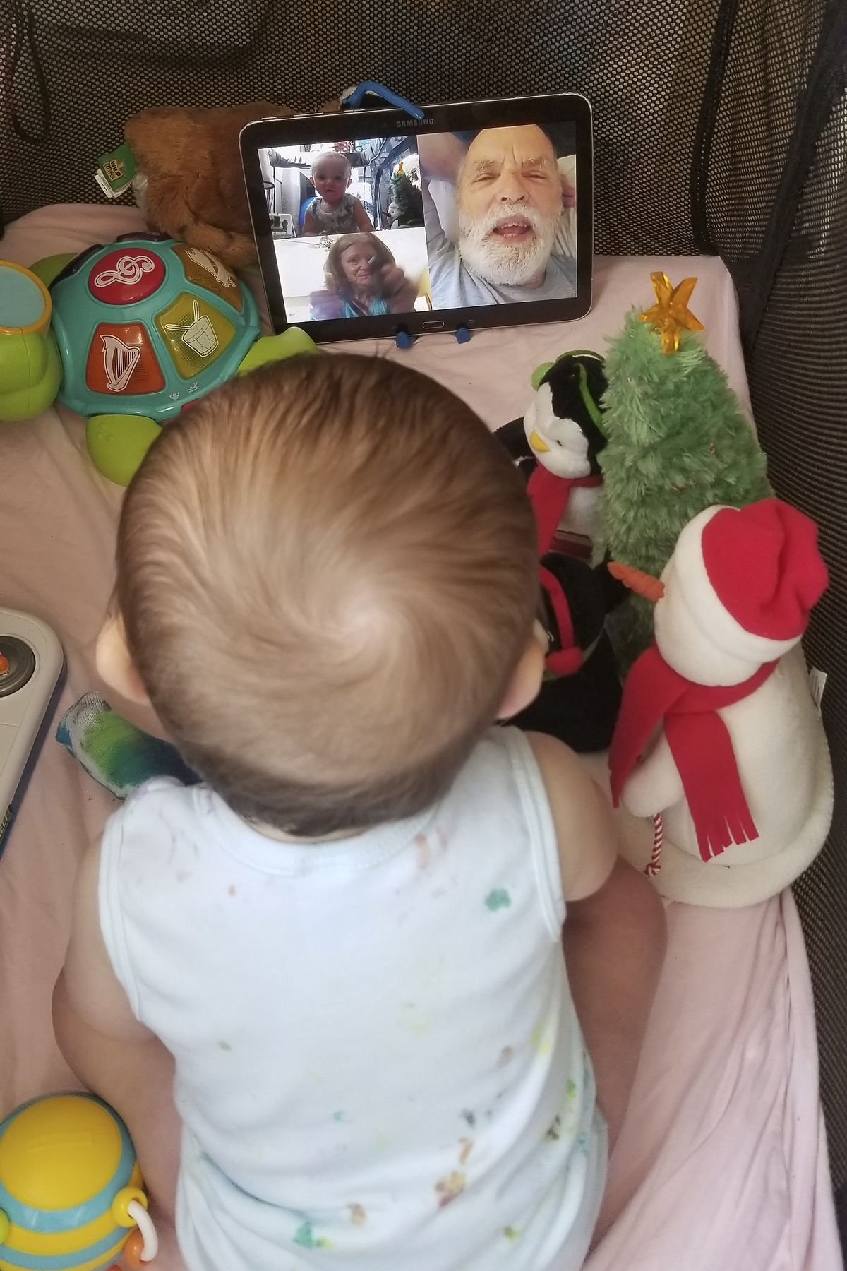 In this photo provided by Julie Bufkin, her 7-month-old boy, Calvin, interacts with his grandparents, Debbie and Allan Cameron, in Chandler, Arizona, on a FaceTime video call from his crib in Tempe, Arizona.