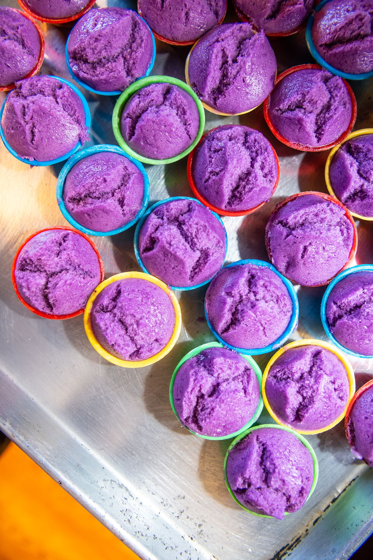 Muffin-shaped puto, sweet steamed rice cakes, show off a deep purple color from ube, a variety of yam.