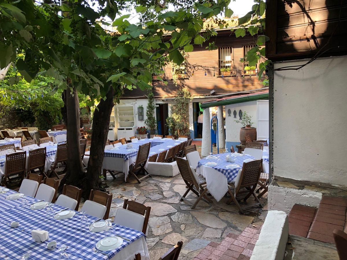 Patio tables set with gingham tablecloths on a stone patio beneath shading trees with a large house wrapping around the courtyard