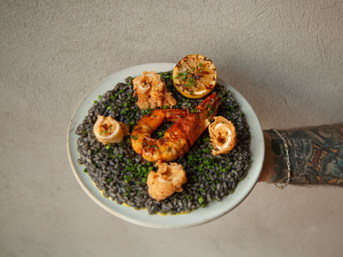 A white plate held up with a hand that has a large piece of shrimp on it, along with lentils and some fried pieces of calamari