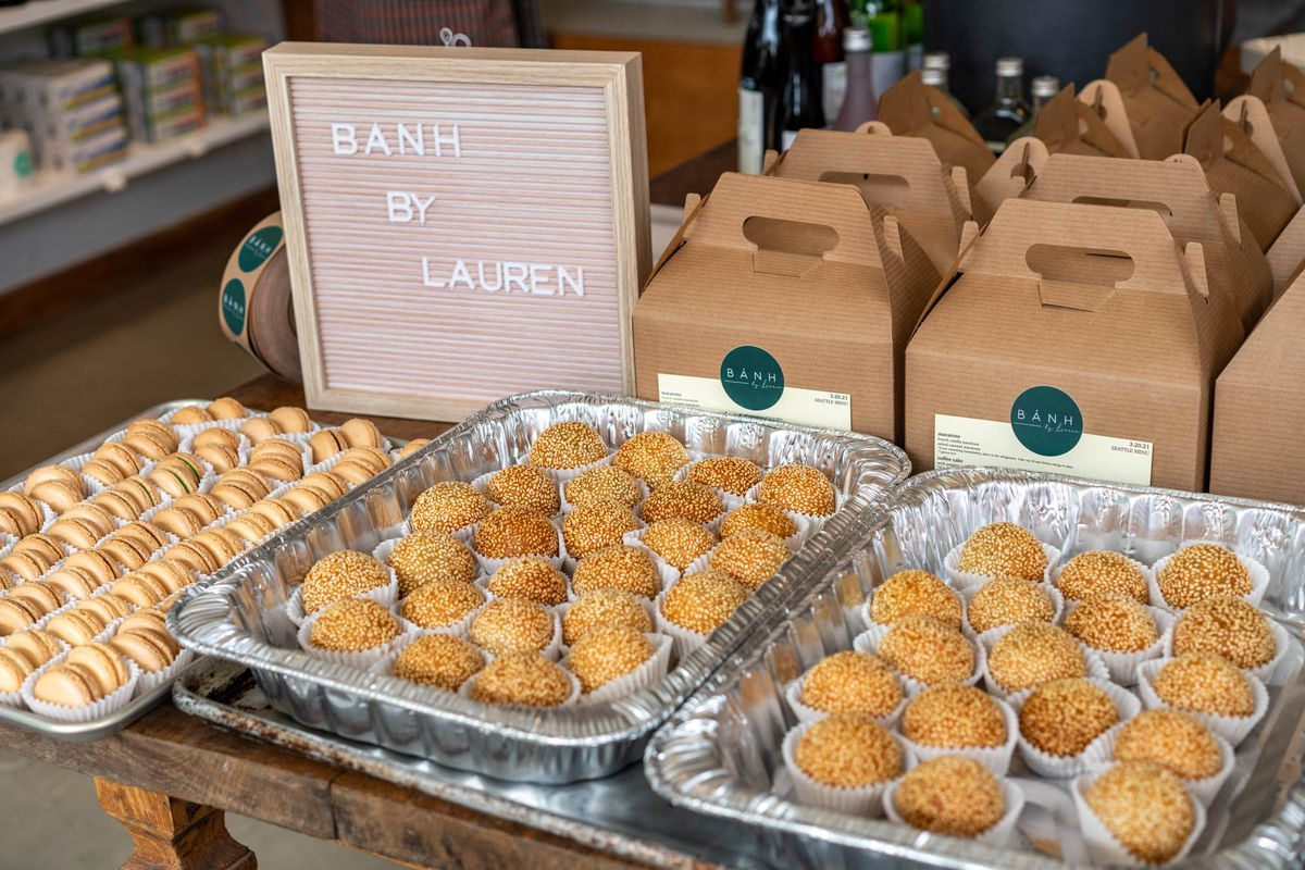 A table with pastries laid out on top, a Banh by Lauren sign set up, and brown boxes lined up in the back