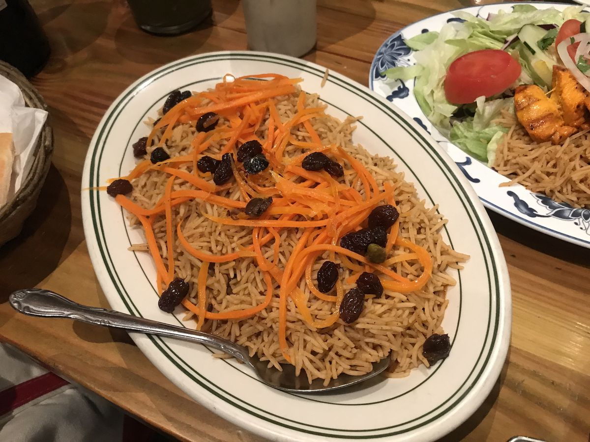 A white plated heaping with Afghan brown rice topped with raisins and slivers of carrots next to a plate with salad greens, rice, and chicken kebabs.