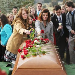 Family members place roses on the casket of former Utah Gov. Olene Walker at the Salt Lake City Cemetery in Salt Lake City on Friday, Dec. 4, 2015. Walker died of natural causes at age 85.