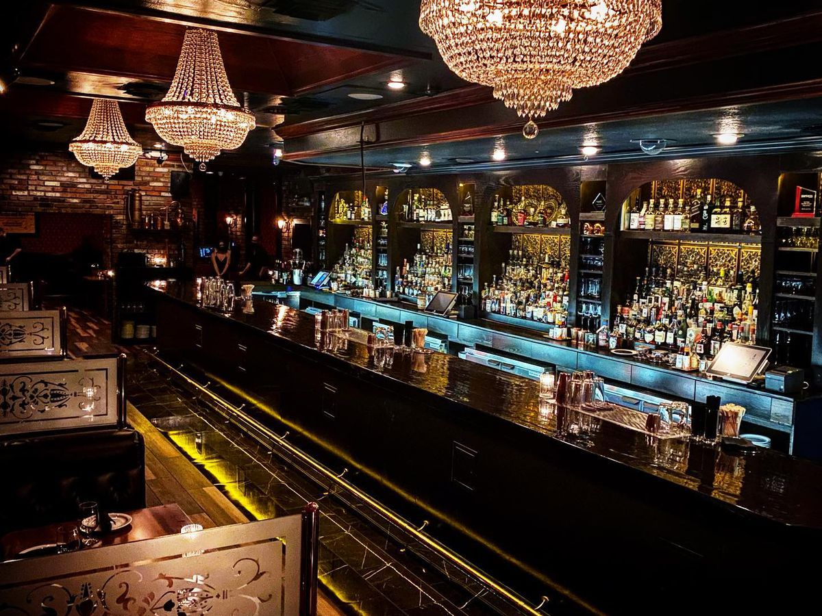 A dark bar with blue neon, mirrors, and chandeliers overhead