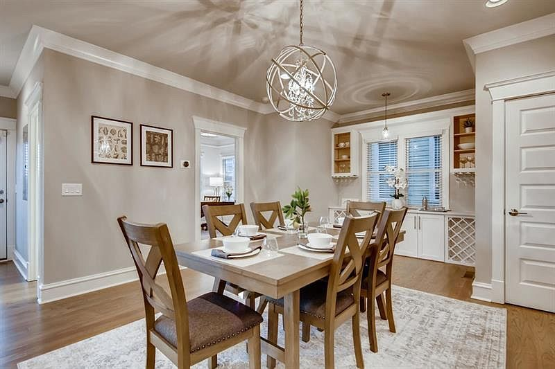A white and beige dining room in a home with a big light above.