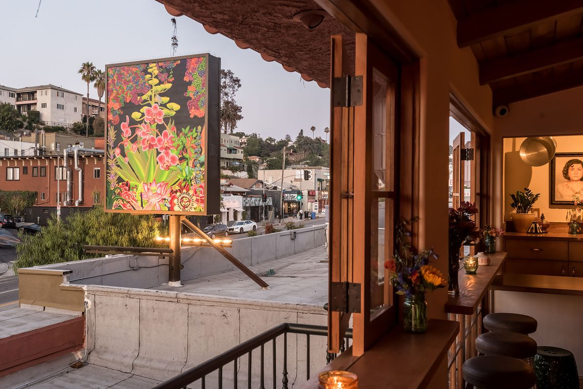 View of Echo Park with a colorful sign and rooftop from Bar Flores.