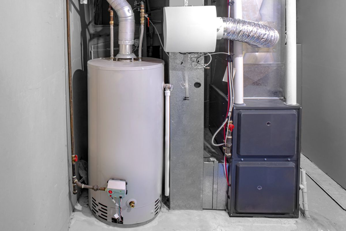 A grey furnace near a water heater and surrounded by other silver-colored home equipment in a grey room.