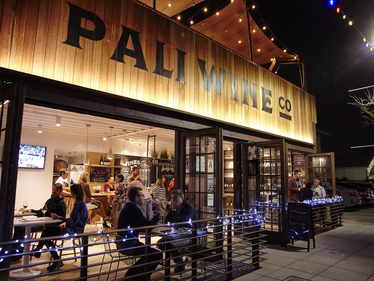 People sitting on the front patio of Pali Wine Co. at night.