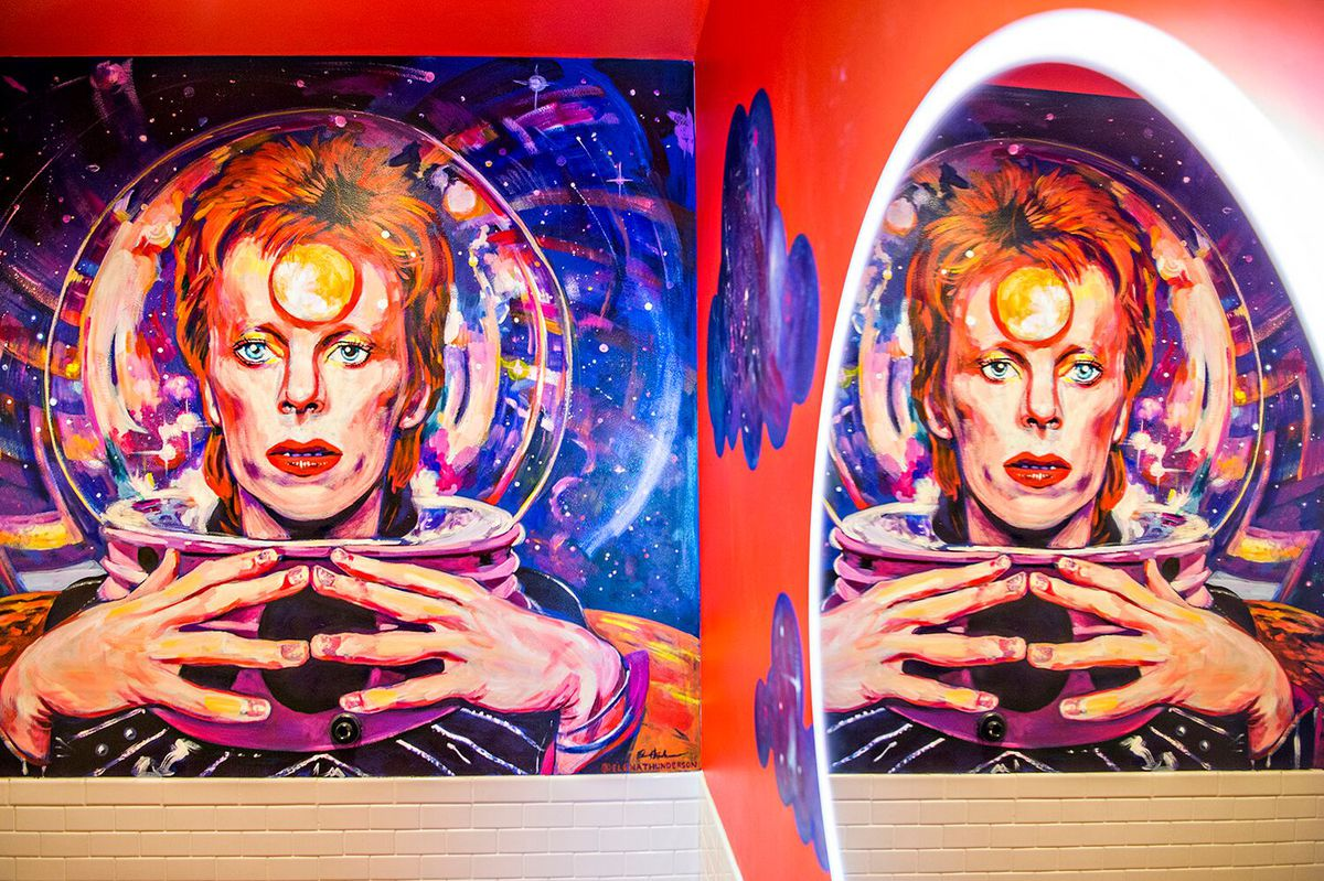 A photo of a large mural of David Bowie that is reflected in the mirror of the bathroom at Somebody People