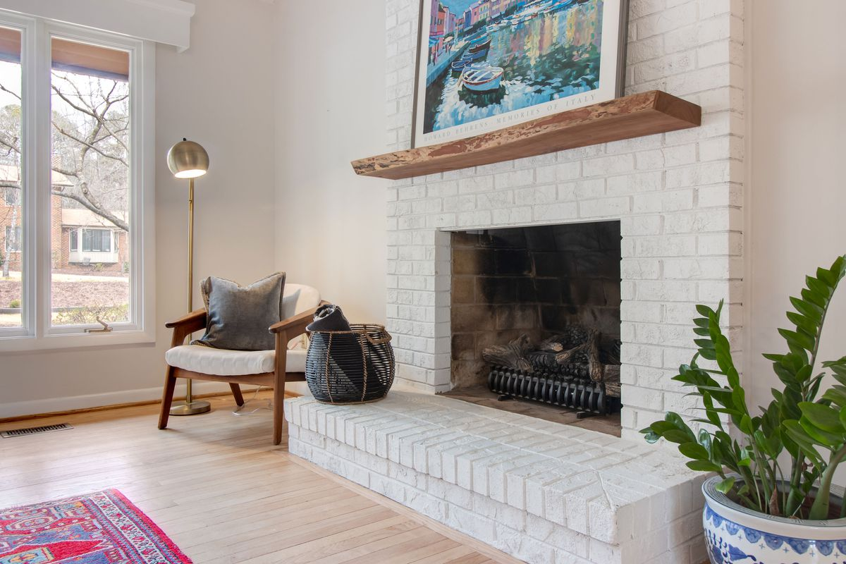A painted brick fireplace in a modern living room.