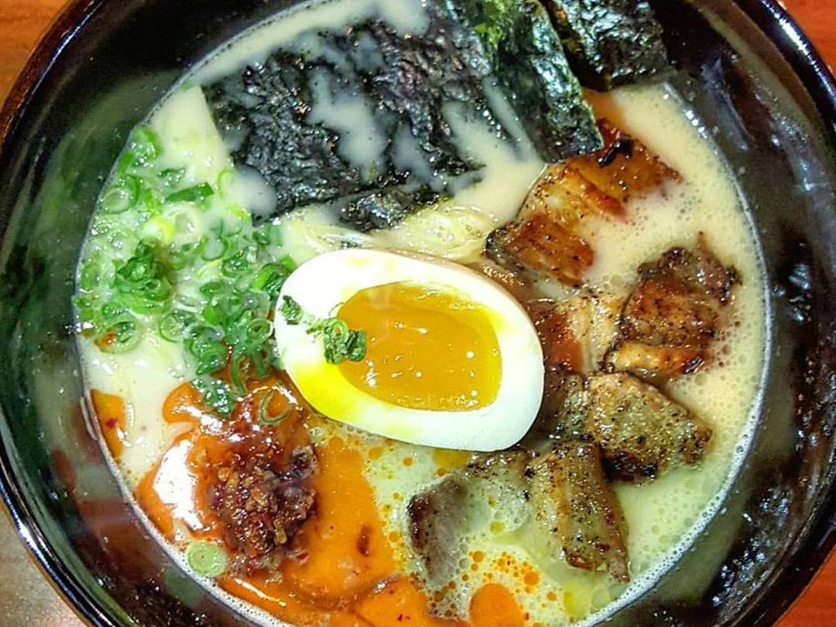Overhead shot of a bowl of ramen with a creamy pale yellow broth, chile oil, soft boiled egg, seaweed, scallions, and crispy pork