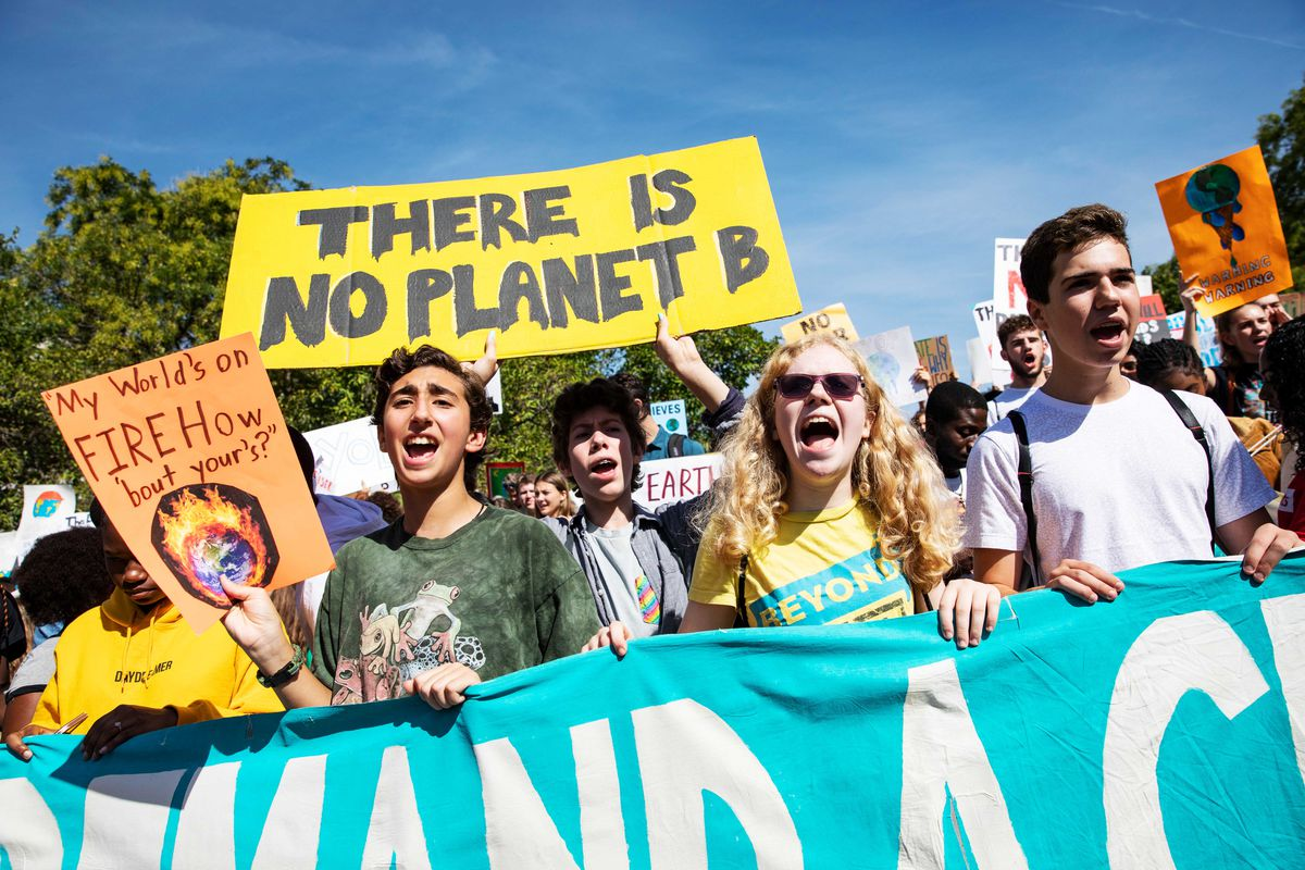 "Global Climate Strike protesters march, chant, and hold signs, one of which reads, ""There is no planet B."""
