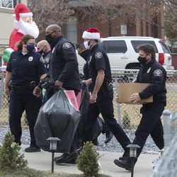 West Valley police officers deliver gifts to families during the department's Giving Tree event in West Valley City on Tuesday, Dec. 22, 2020. The program provided gifts for 159 children from 51 low-income families in the city that were delivered to their homes by police officers. Each child started with a list of needed items and holiday wishes. Santa's helpers from the police department, local businesses and the community then worked hard to fulfill the wishes.
