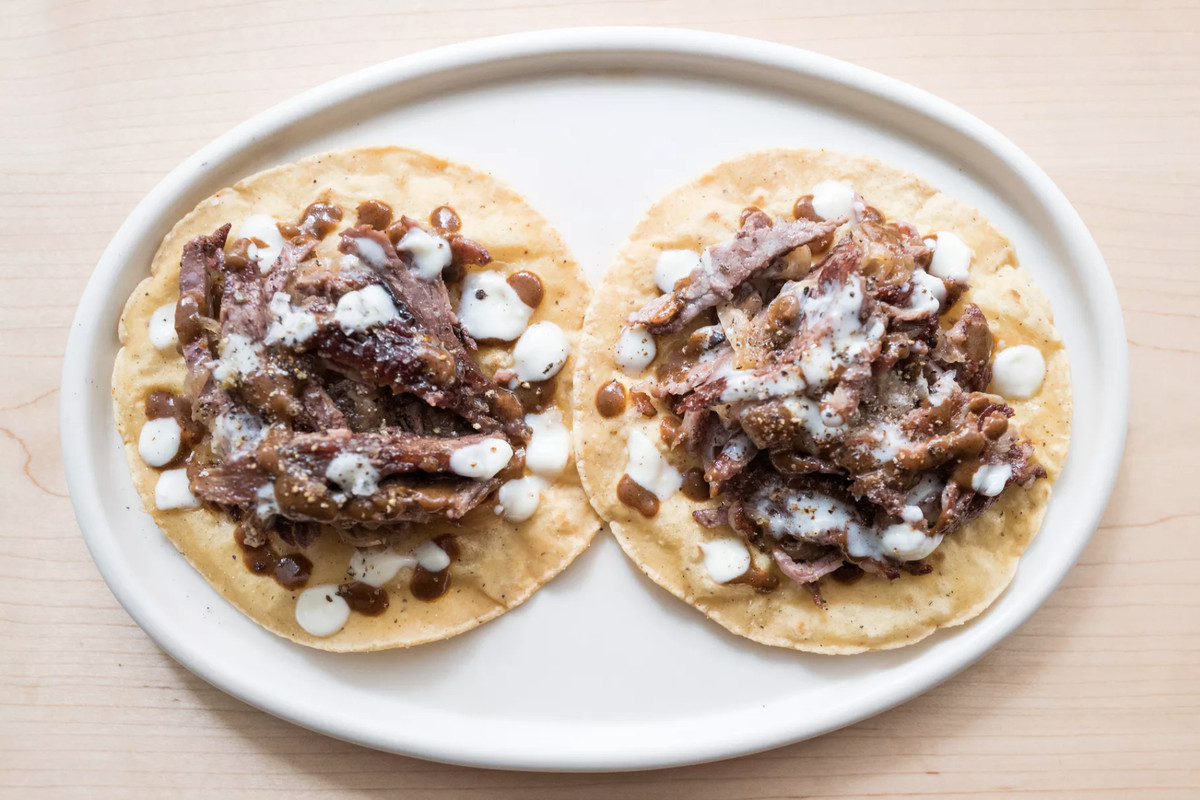 An overhead photograph of two meaty tacos on a white plate