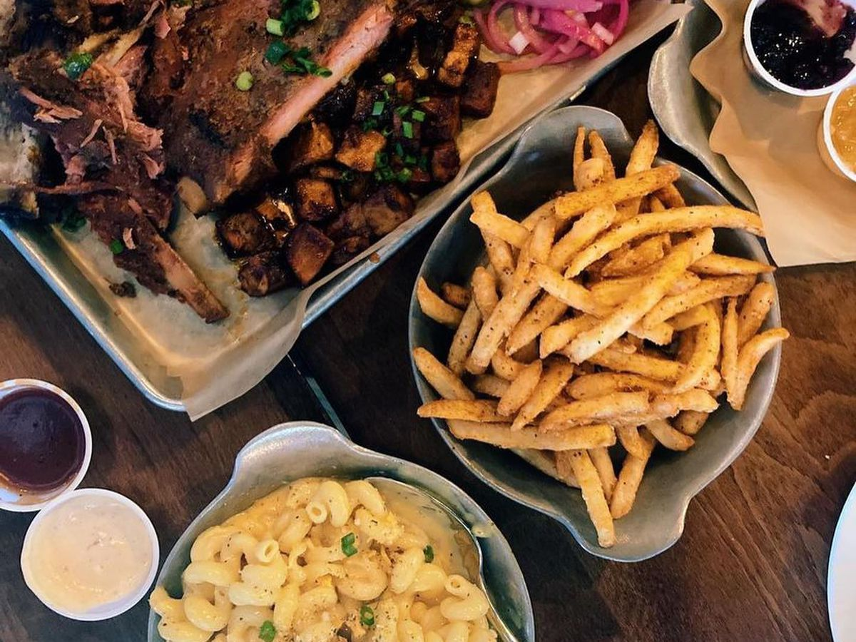 A paper-lined silver tray with brisket, mac and cheese, and fries.