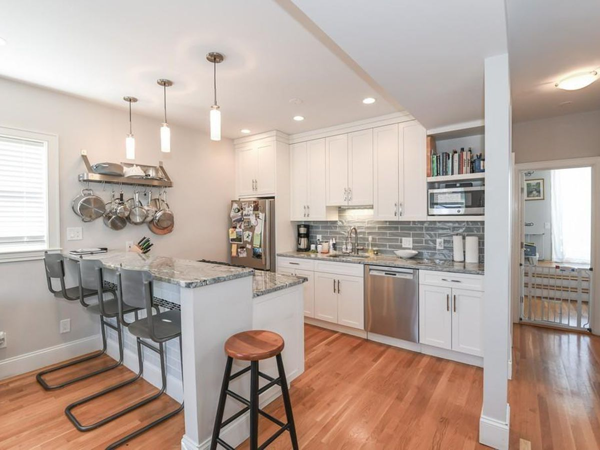 An open kitchen with a countertop that has three stools in front of it.