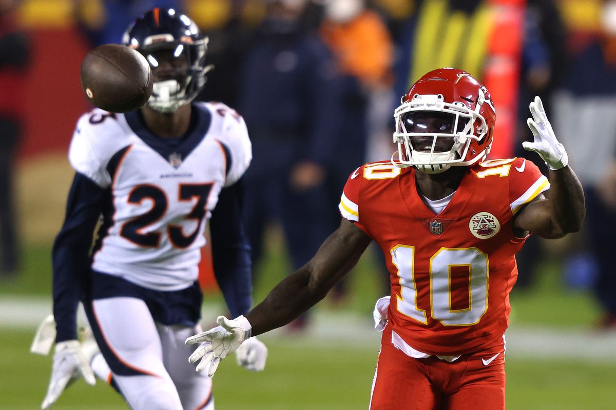 Tyreek Hill #10 of the Kansas City Chiefs attempts a catch in front of Michael Ojemudia #23 of the Denver Broncos during the first quarter of a game at Arrowhead Stadium on December 06, 2020 in Kansas City, Missouri.