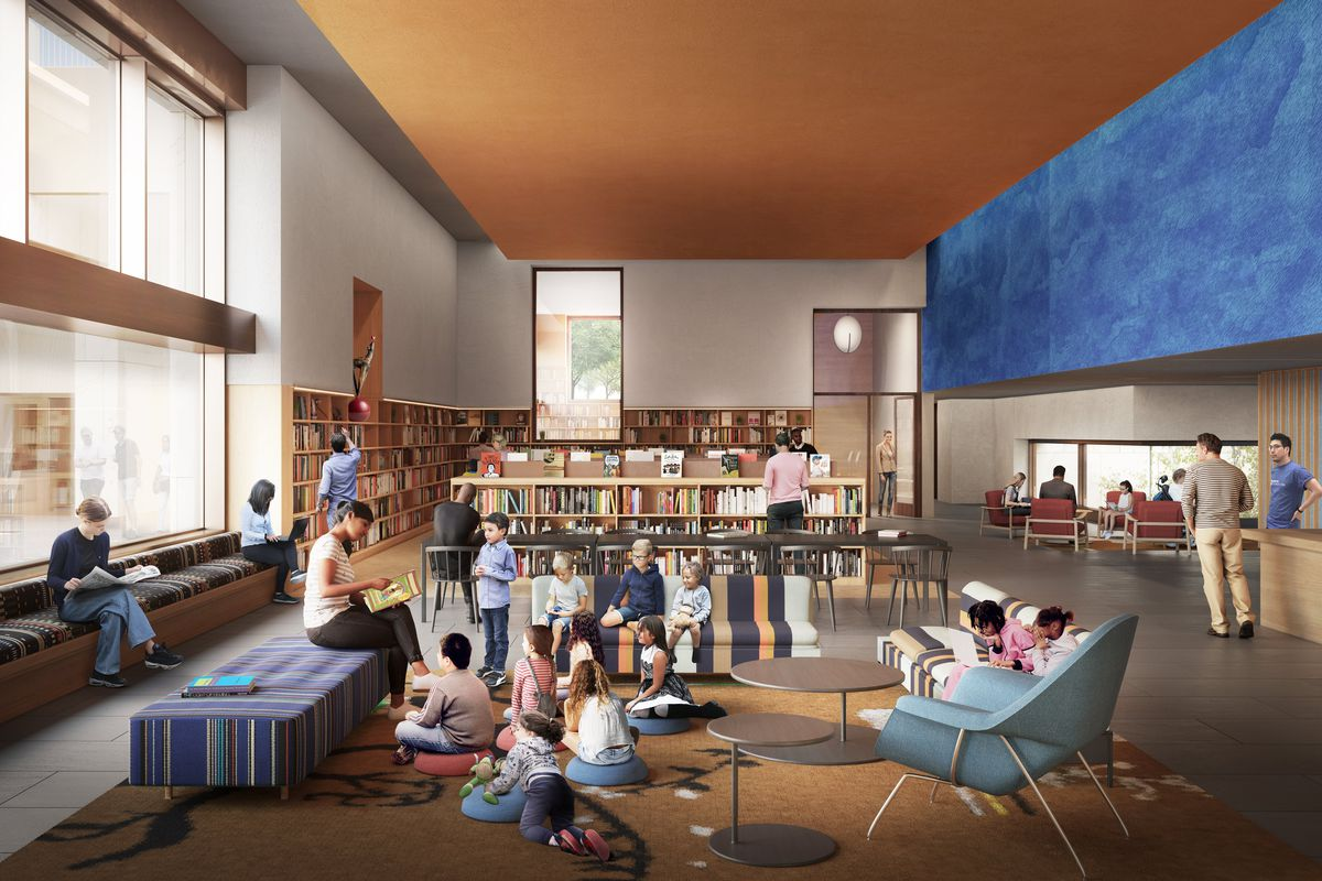 Children sit around a librarian in a large room with bookshelves, seating areas, an information desk, and oversized windows.