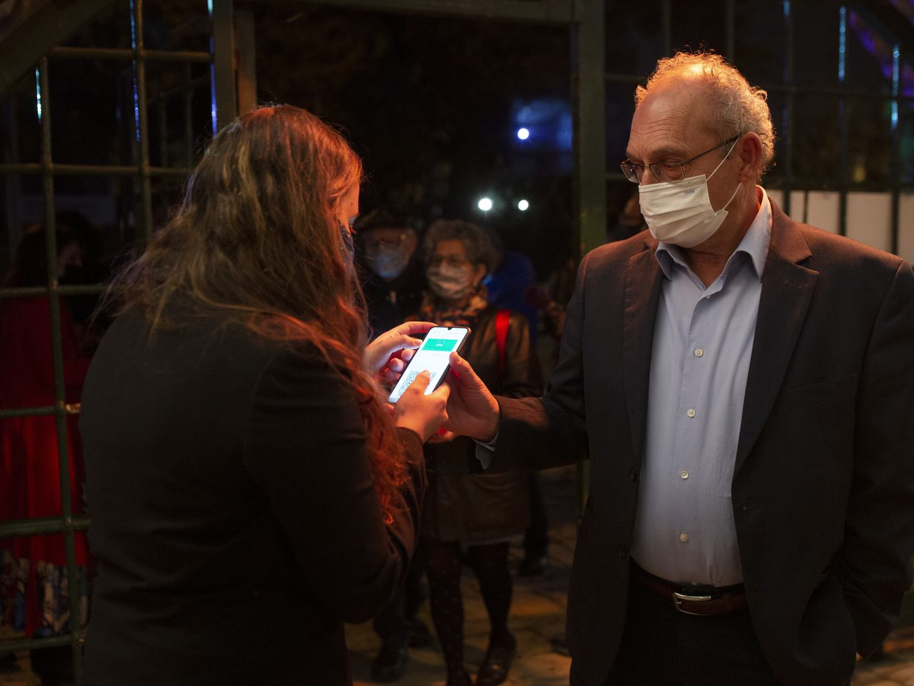 "A man presents his ""green passport,"" proof that he is vaccinated against the coronavirus, on opening night at the Khan Theater for a performance where all guests were required to show proof of vaccination or full recovery from the virus, in Jerusalem, Tuesday, Feb. 23, 2021."