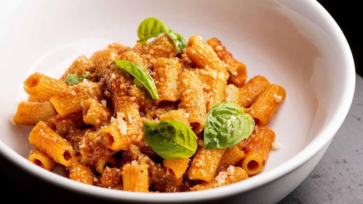 A white bowl of rigatoni with basil leaves in a white bowl.