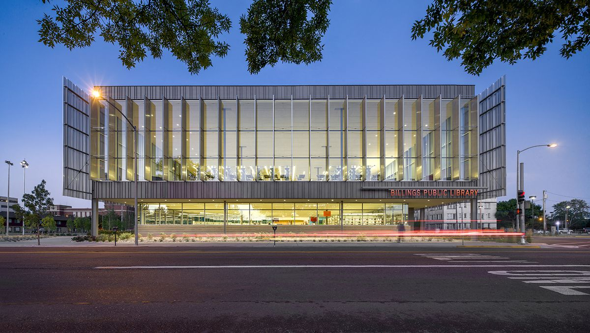 The exterior of the Billings Public Library in Montana. The walls are glass windows and the roof is flat.