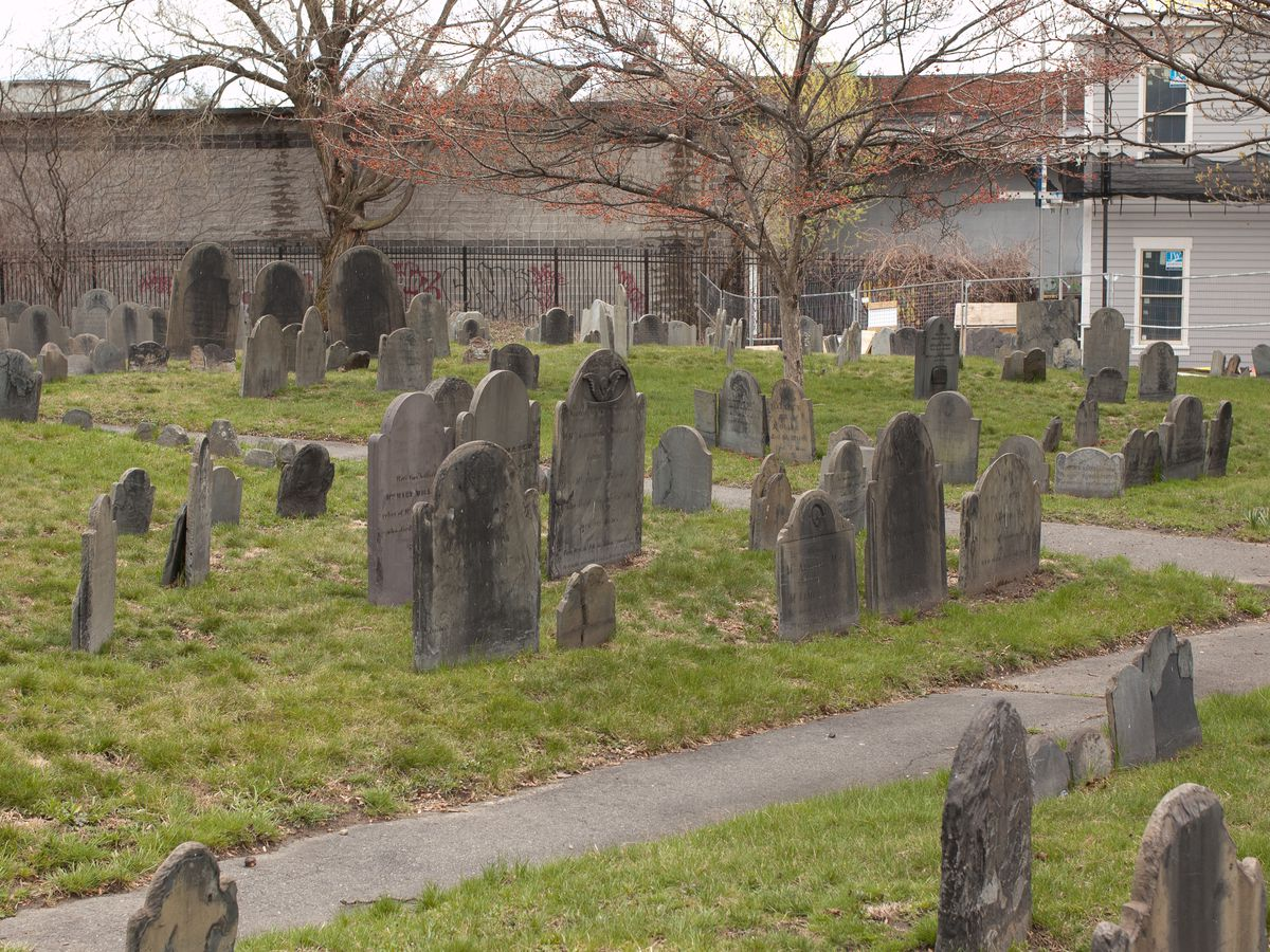 Uneven rows of old headstones, with a footpath among the headstones.