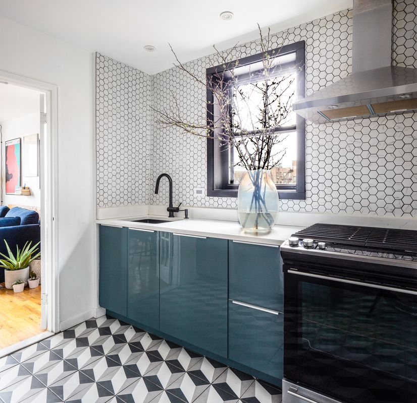 A kitchen with black and white tiles.