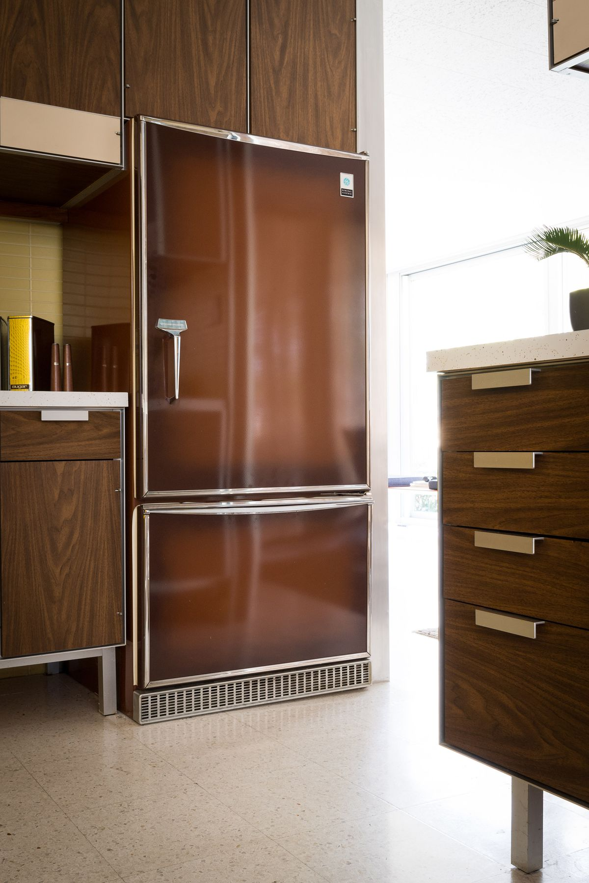 A chocolate brown refrigerator is in the kitchen.