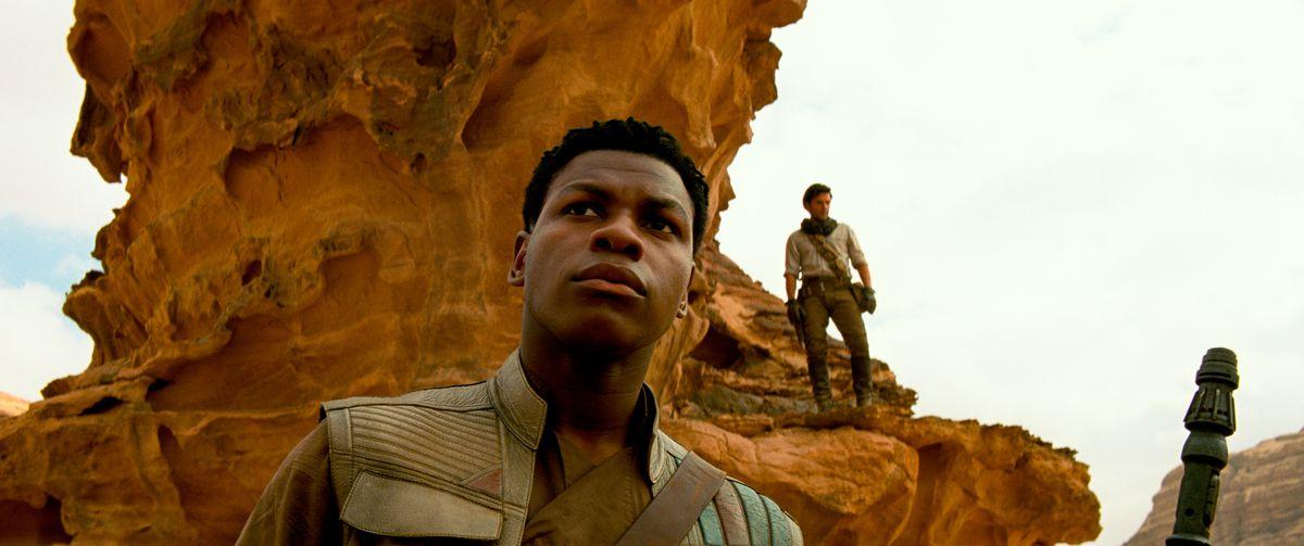 Finn (John Boyega) with Poe (Oscar Isaac) on a ridge behind him in Star Wars: The Rise of Skywalker