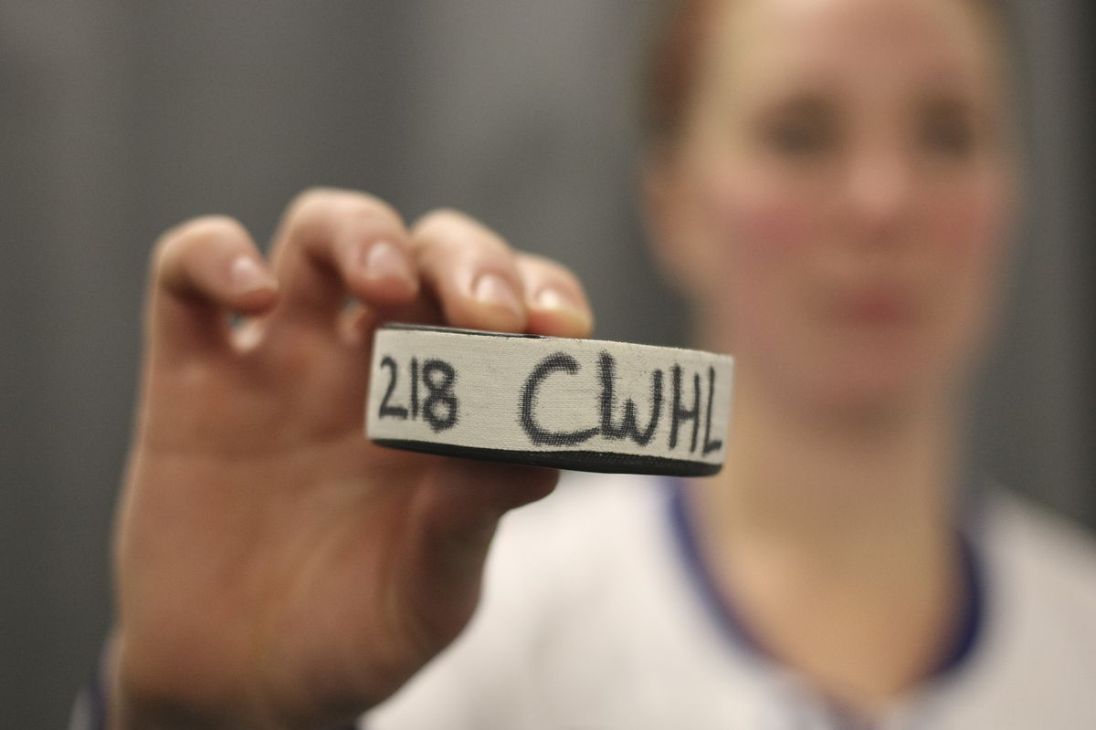 """Shannon Moulson out of focus in the background. In the foreground is the game puck from her 218th game, labelled """"218 CWHL"""""""