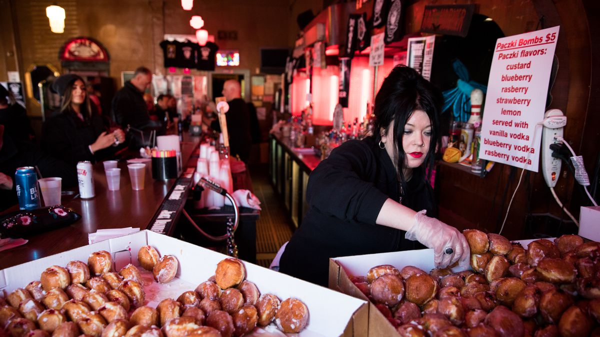 A bartender at Small's selects a paczki from a large and very full box.