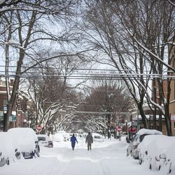 Two people walk down the middle of a snow covered street on W. Cornelia Ave. in in the Lakeview neighborhood, Tuesday, Feb. 16, 2021.