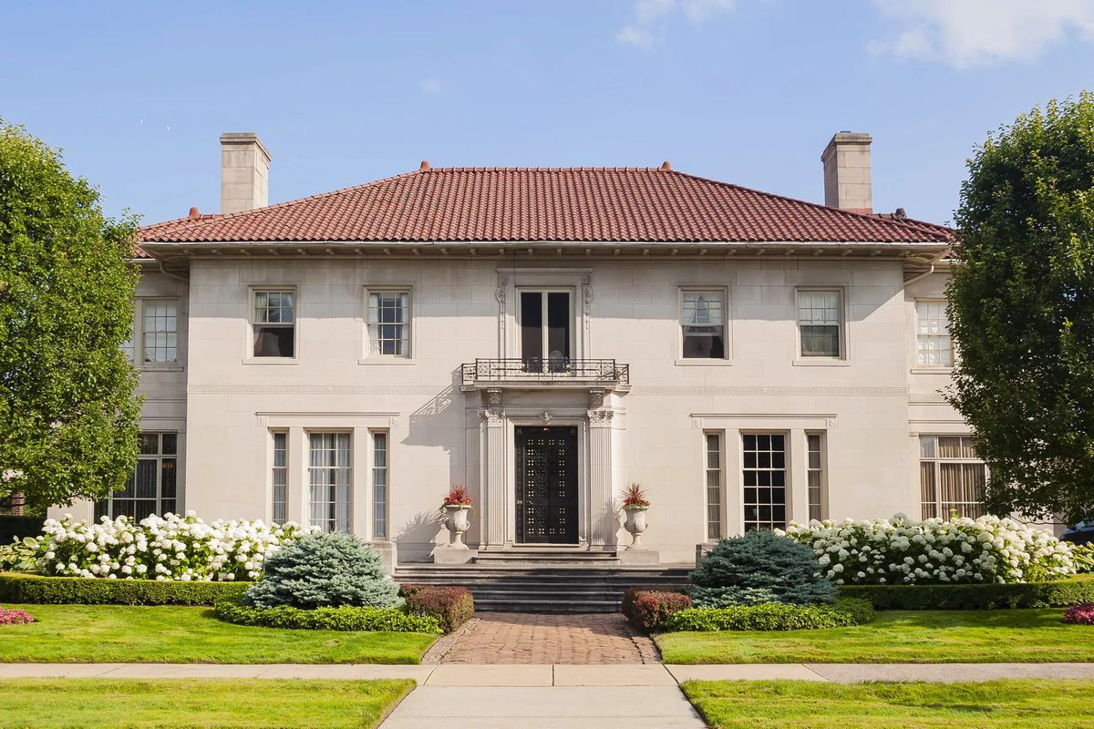 A beautiful stone home with a classical exterior and clay shingled roof.
