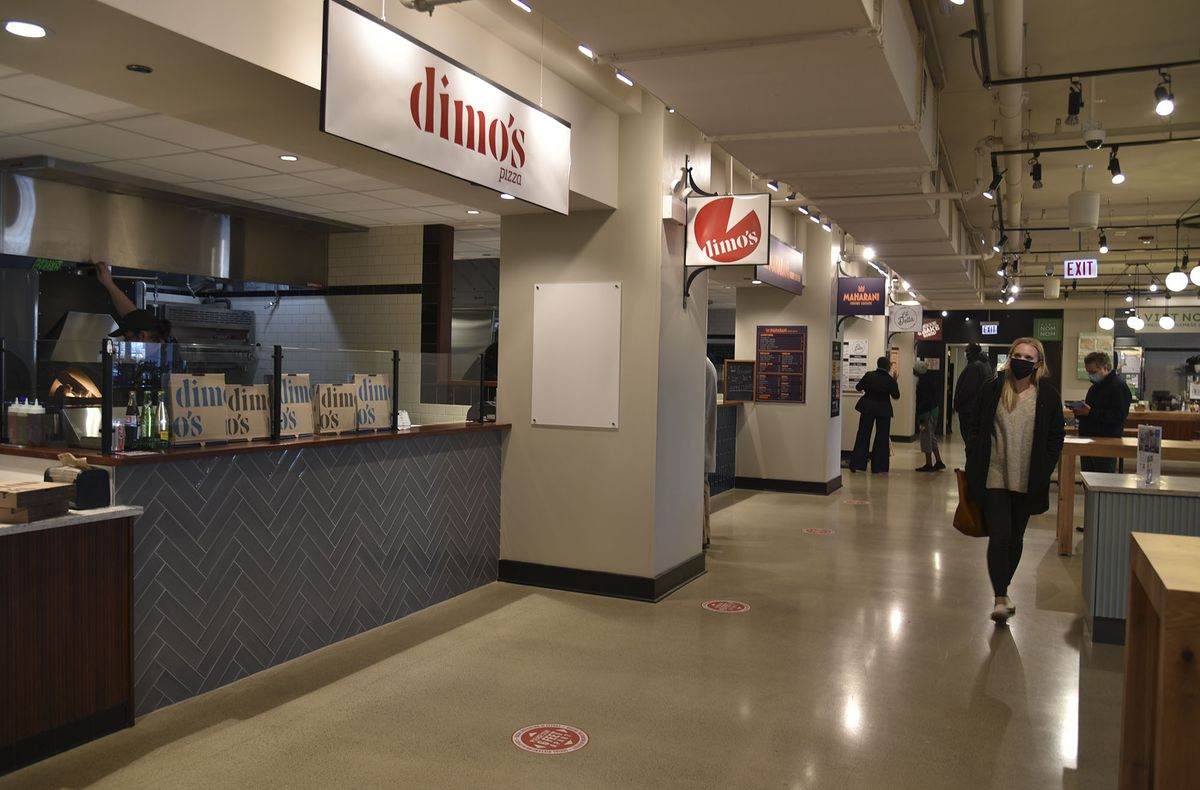"""A stall inside a food hall with a sign overhead that reads """"Dimo's Pizza"""""""