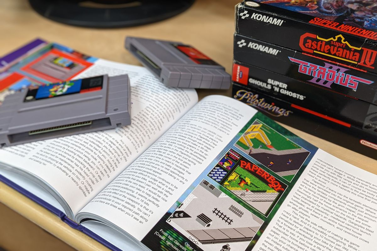 A photo of Super NES Works, a book about the history of Super Nintendo games. A copy of Super Mario World sits on the opened book.