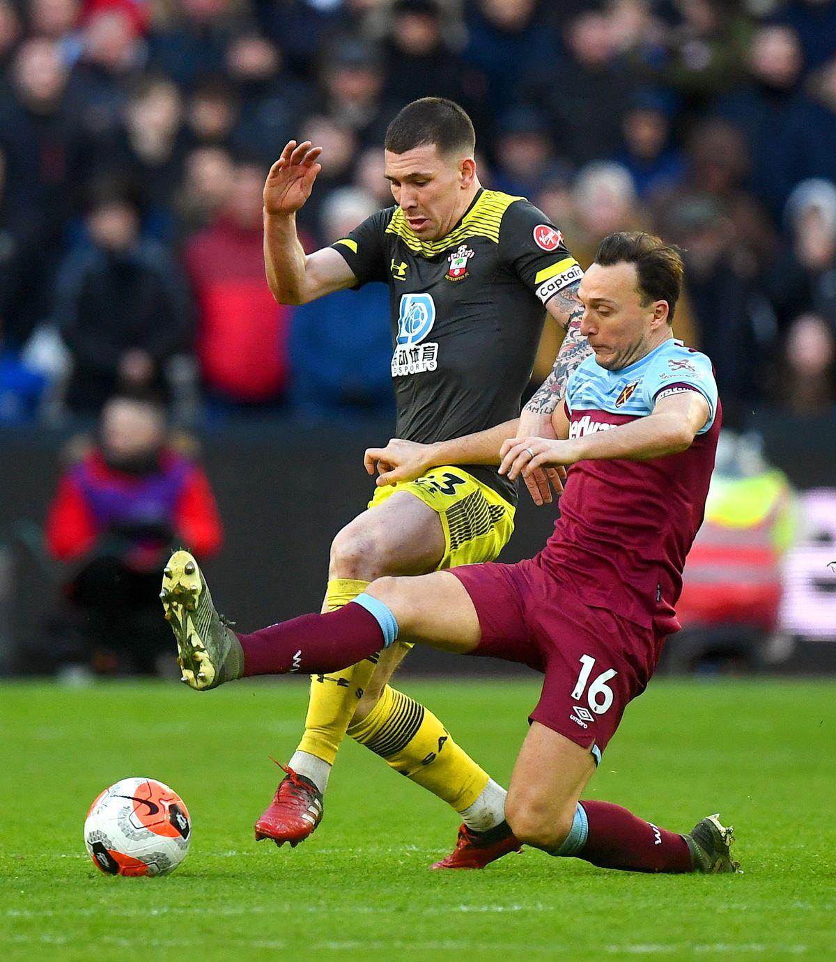 Southampton captain Pierre Emil Hojbjerg challenges West Ham's Mark Noble for the ball Premier League contract