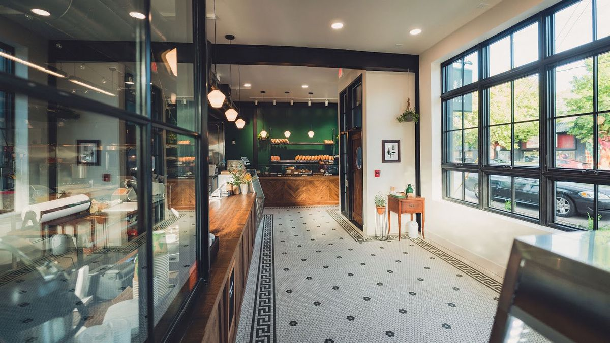 The green and white walled interior of Evergreen Butcher and Baker in Kirkwood Atlanta with white and blue tile floors, butcher counter, and butcher and baked goods cases