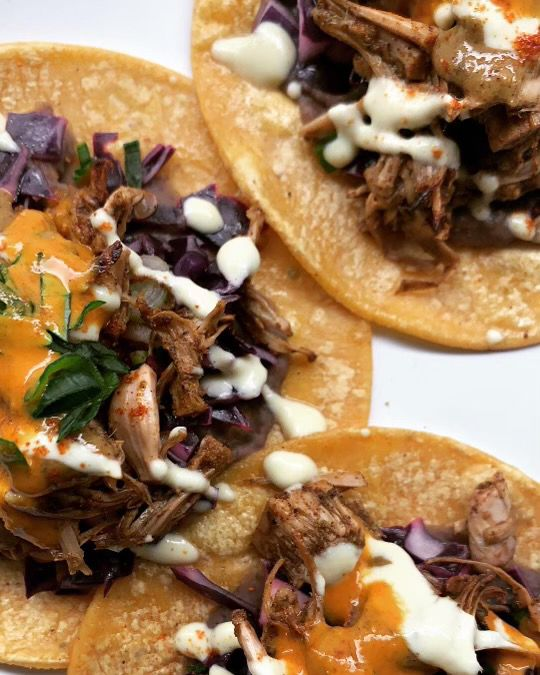 A picture of jackfruit tacos, shredded to look like pulled pork, with crema and a bright orange salsa at Plant Based Papi