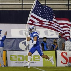 A BYU player carries a U.S. flag onto the field at the start of the team's NCAA college football game against Troy on Saturday, Sept. 26, 2020, in Provo.