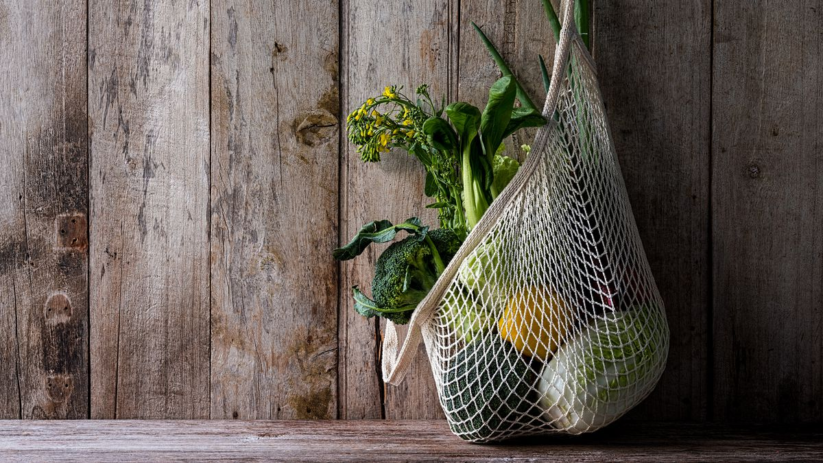 Vegetables in a string bag hanging from a hook on a plank wall.