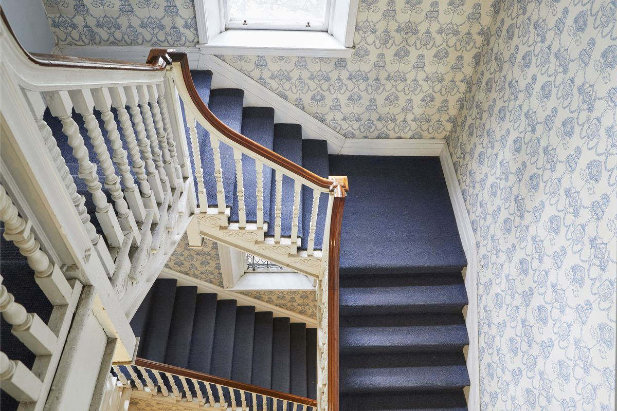 For a story on how to remove wallpaper, an overhead image of a staircase with dark blue carpeting and blue and white patterned wallpaper.