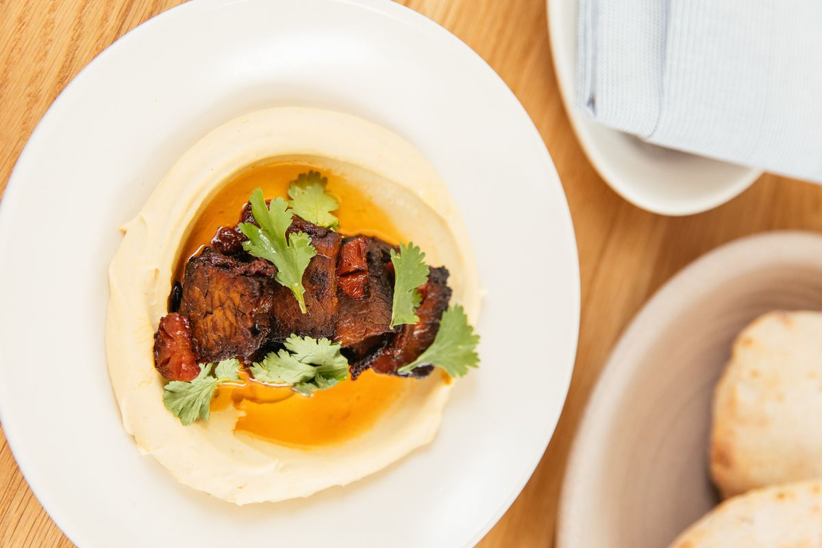 Slices of tender beef brisket sit atop a silky pool of hummus and herbs on a white plate.