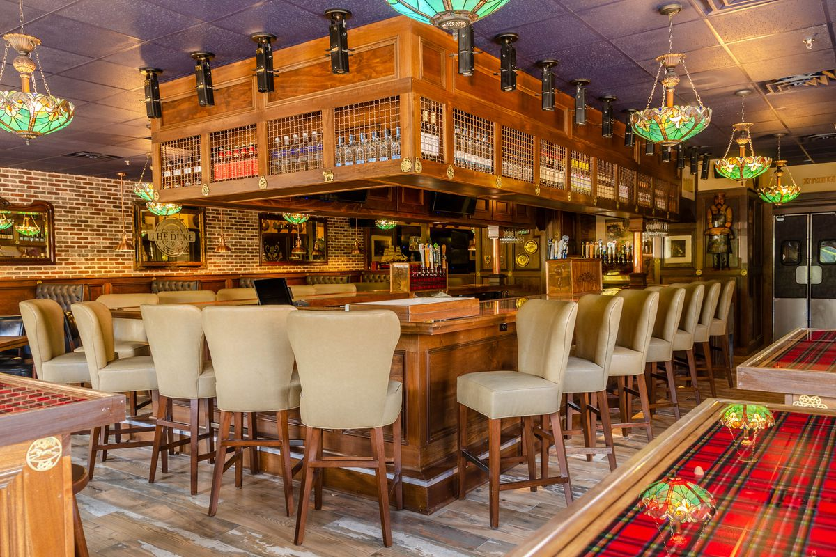 Looking toward the large wooden bar surrounded by beige leather bar chairs