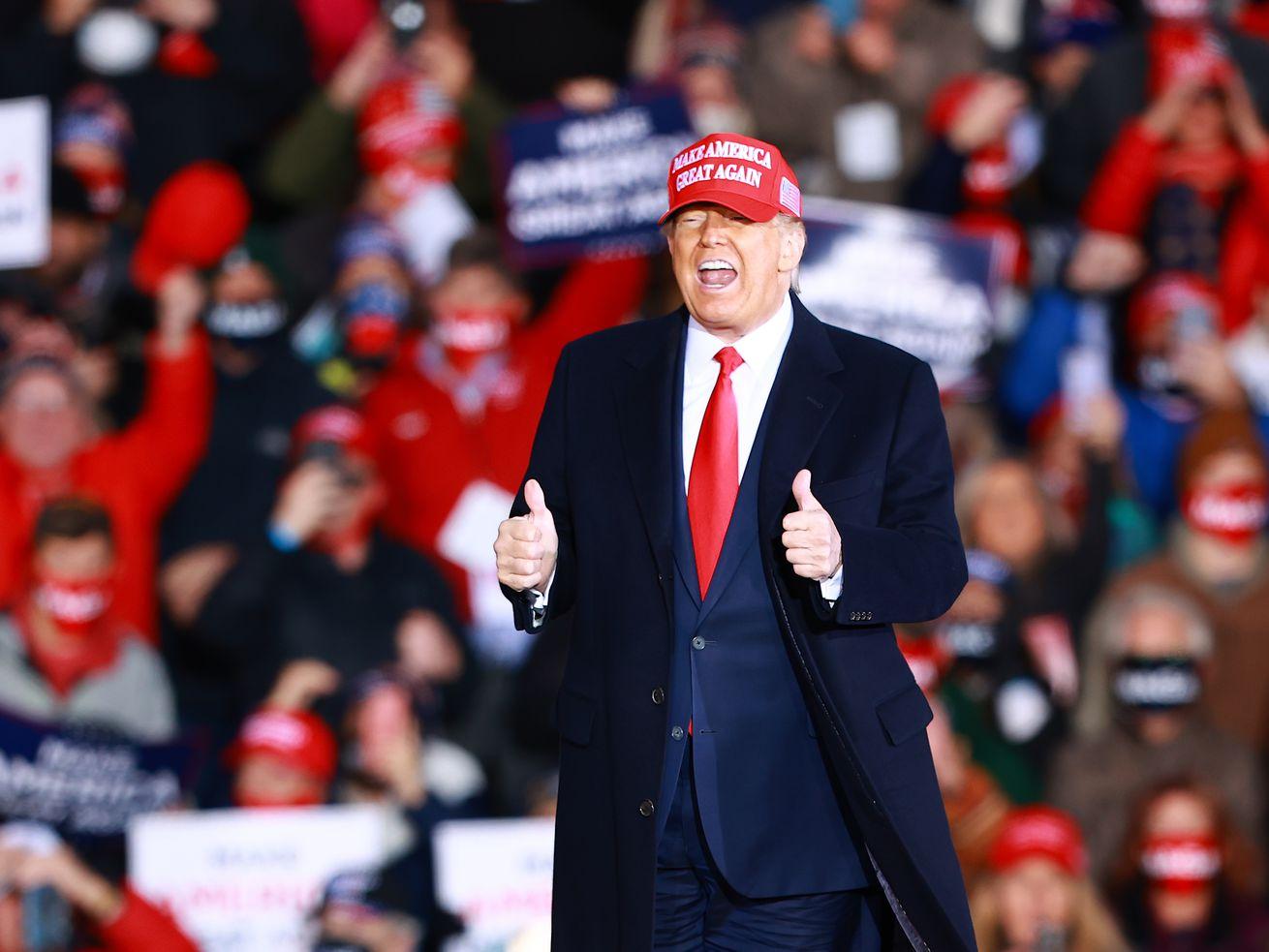 Le président Trump, faisant des gestes et parlant, porte un chapeau rouge MAGA, un costume bleu marine et un pardessus sombre devant une foule de ses partisans.