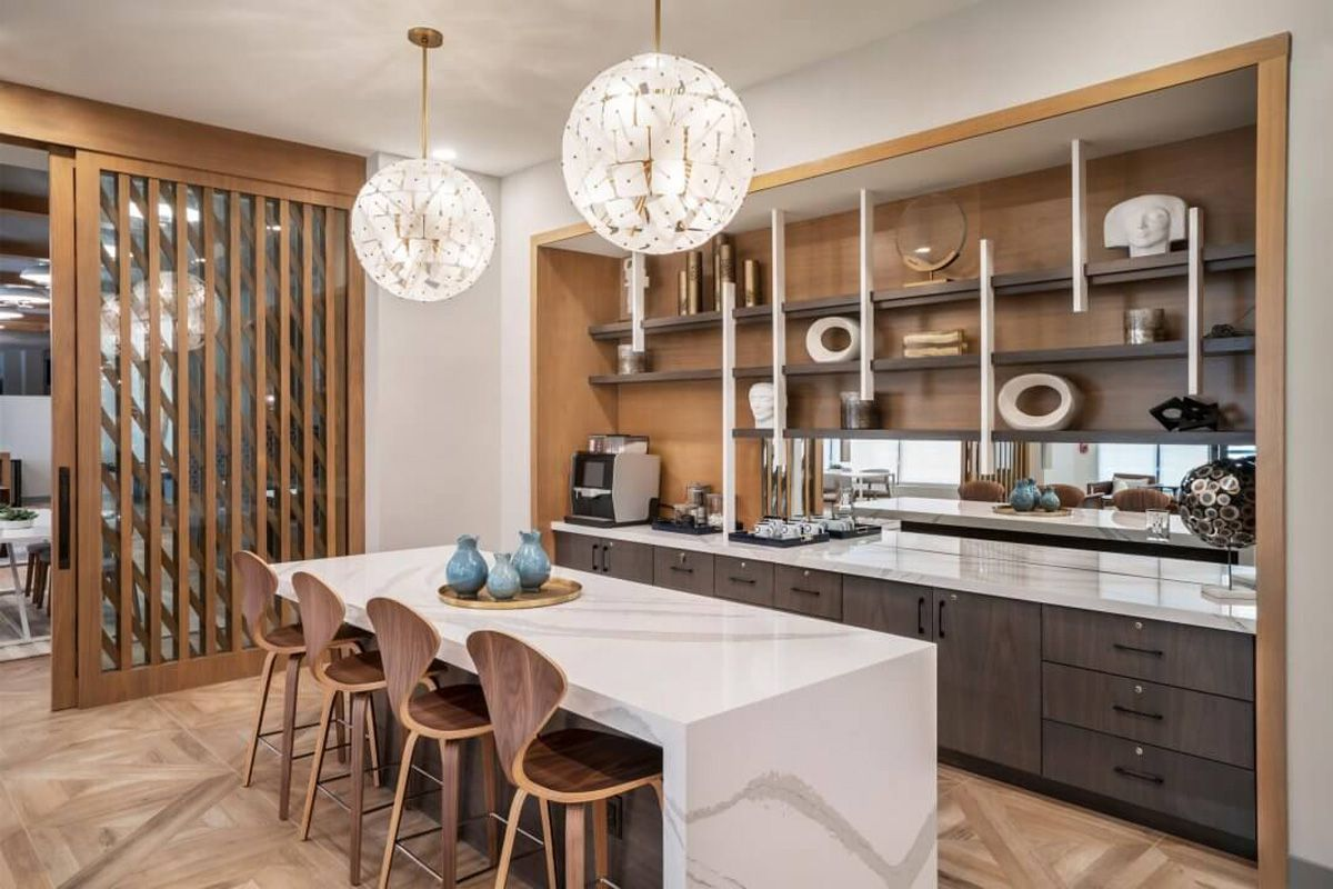 A coffee bar with marble kitchen island and wooden chairs and shelves.