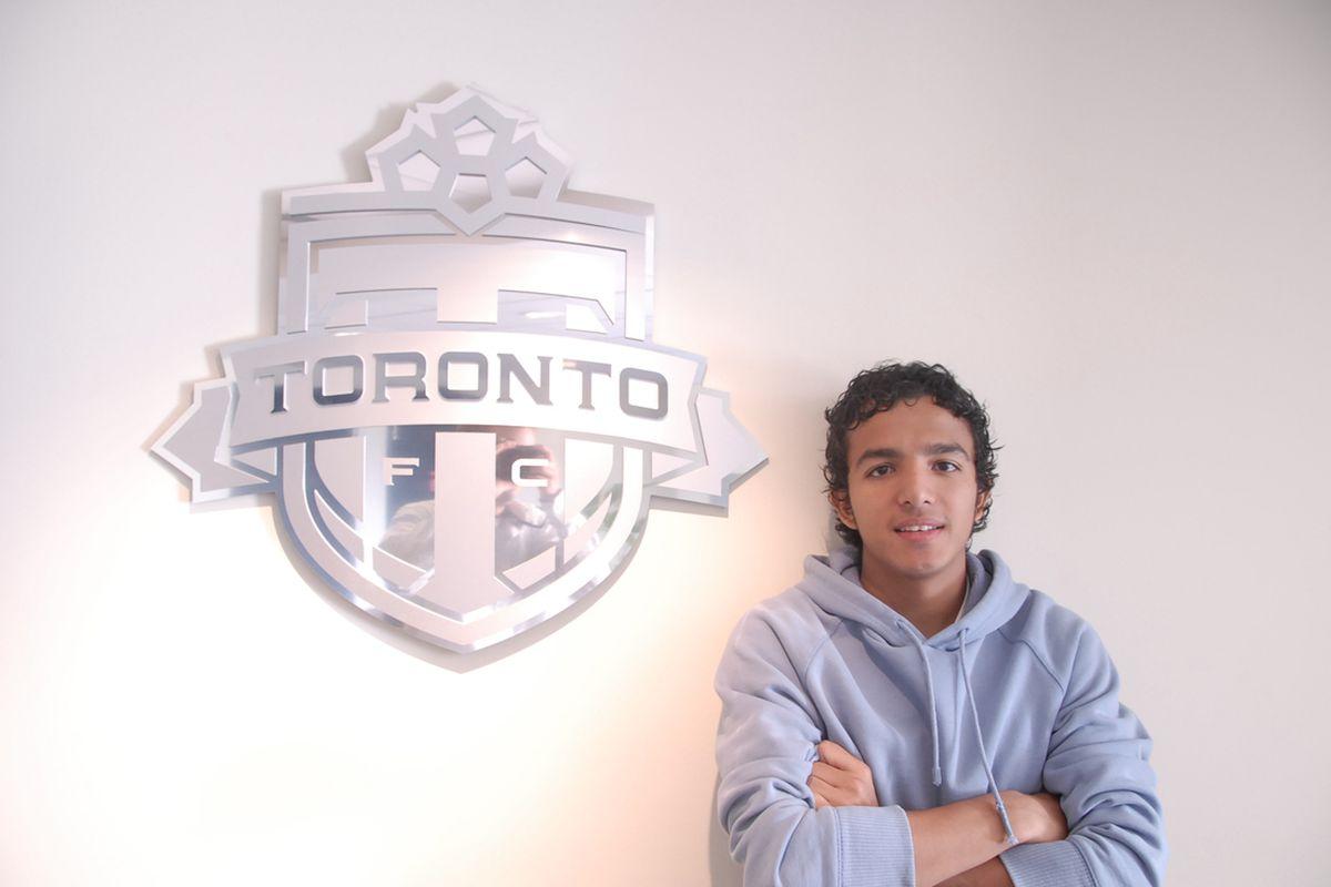 Oscar Cordon posing beside a Silver TFC logo inside the majestic second floor lounge of BMO Field.