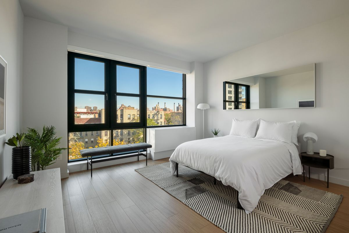 A bedroom with a large bed, large windows, hardwood floors, and planters.