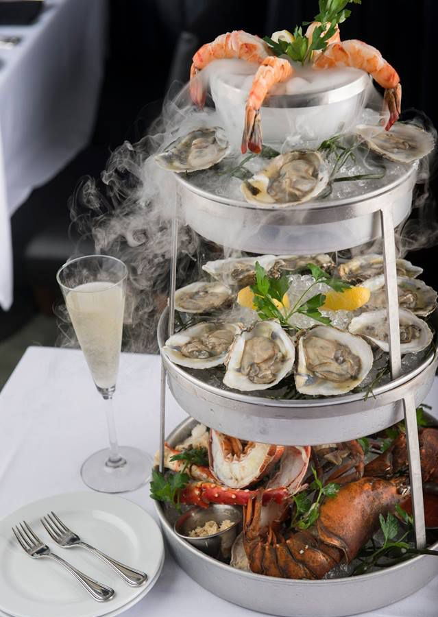 Three-tiered seafood tower with a smoking effect thanks to dry ice. A glass of champagne sits next to it.